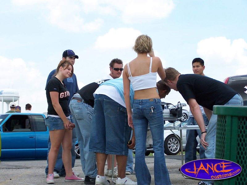 A crowd of people around a model car? I'm sure they were just checking out the blonde.